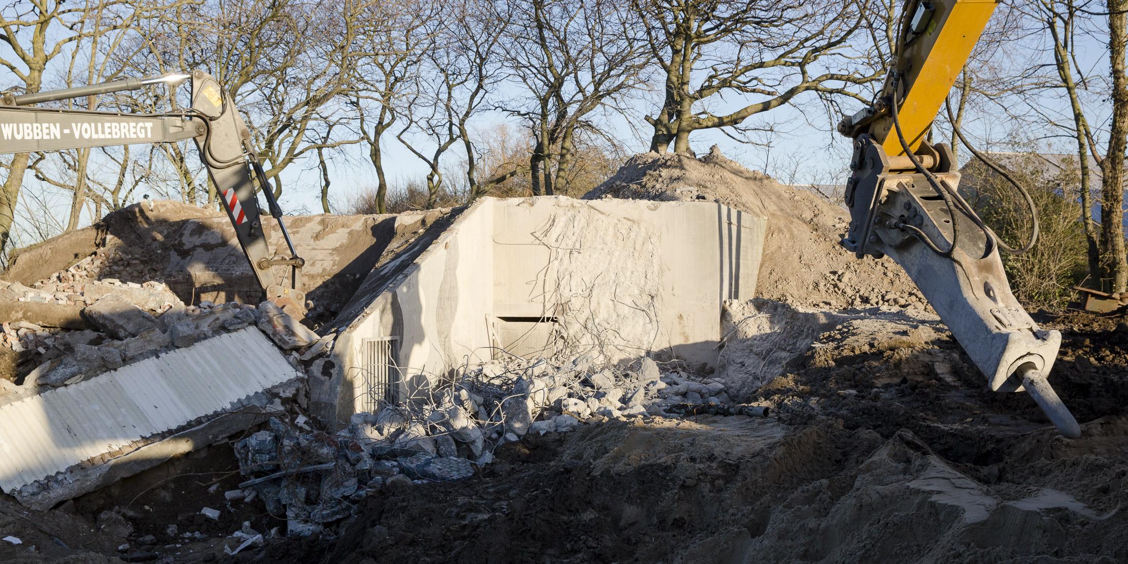 Een betonnen bunker wordt gesloopt.